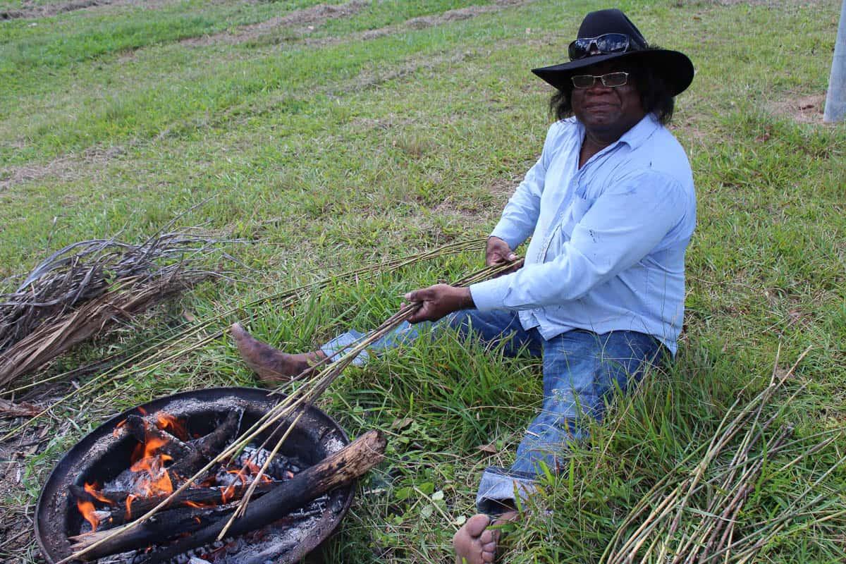 Abe Muriata heating the cane; photo Valerie Keenan, Girringun Aboriginal Art Centre