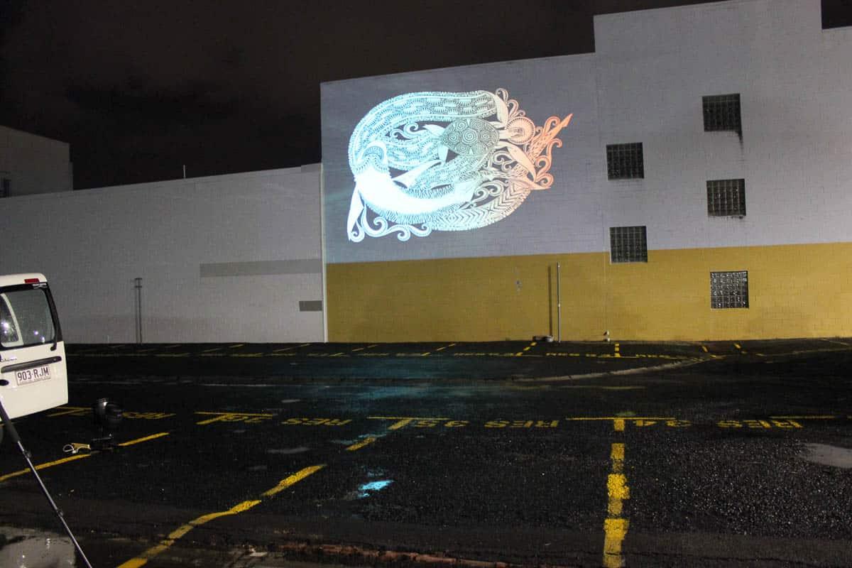 A Glen Mackie linocut print projected on a Cairns Street wall.
