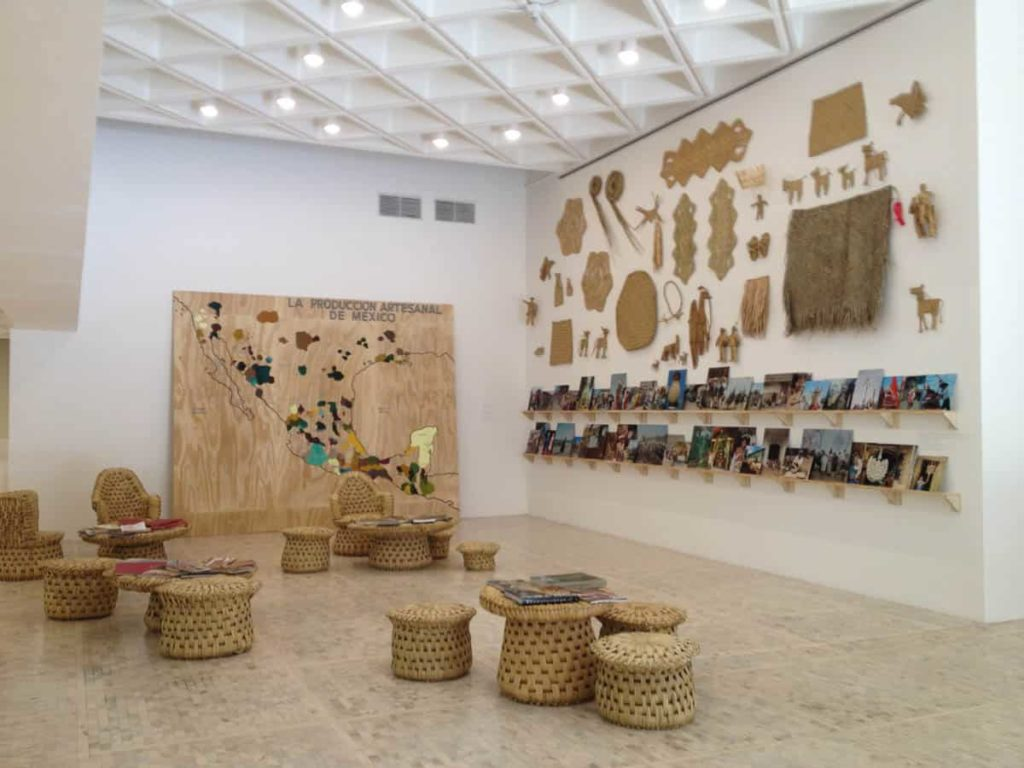 Painted map, reed tables and chairs, books, ethnographic photos, woven reed items