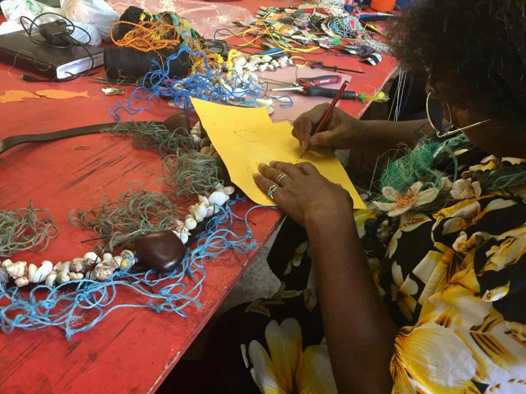 Artist Florence Gutchen working on her lei Home Reef at the Erub workshop