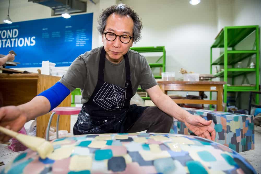 Choi, Seung Jae reworking surface for second glaze firing