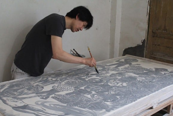 Sun Koo Yuh working on a large porcelain tile while in China in preparation for his exhibition at Gimhae Clay Arch