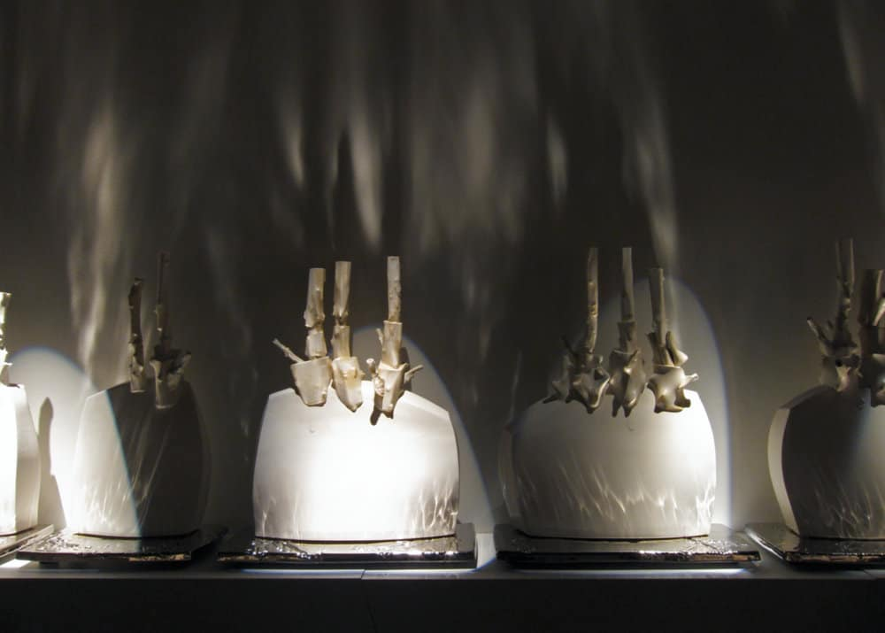 Trudy Golley, (a)blaze, detail, slip-cast and press-molded glazed porcelain with titanium PVD (Physical Vapour Deposition), painted wood shelving, high intensity gallery lighting, .65 x 6.4 x .25m, photo by Paul Leathers, made in Jingdezhen, China and Red Deer, Canada