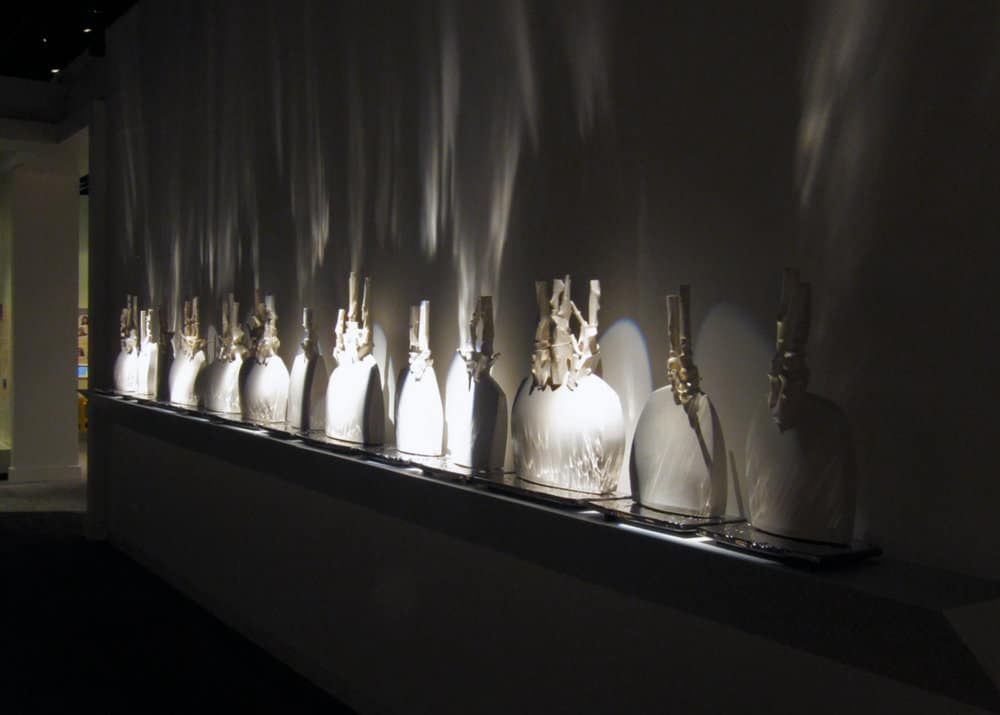 Trudy Golley, (a)blaze, overview, slip-cast and press-molded glazed porcelain with titanium PVD (Physical Vapour Deposition), painted wood shelving, high intensity gallery lighting, .65 x 6.4 x .25m, photo by Paul Leathers, made in Jingdezhen, China and Red Deer, Canada