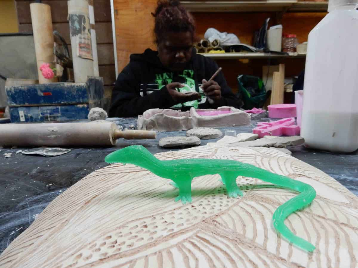 Marissa Thompson, Lizard sculpture in resin, with her sister Anne Thompson working on jewellery in background, Ernabella Arts, 2014, photo: Emily McCulloch Childs
