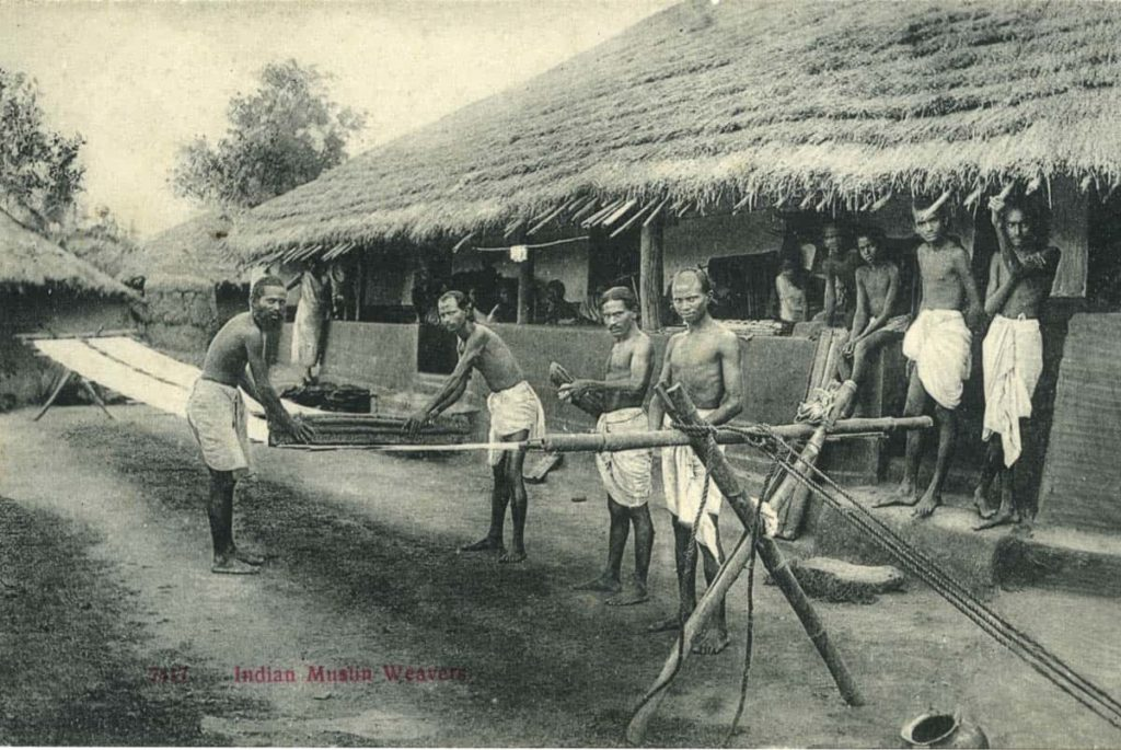 pg 97	Indian muslin weavers. Indian muslin weavers, outside their thatched houses, busy with final processing of the fabric.  Reproduction from postcard, Photographer : Unknown
