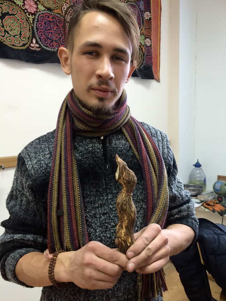 Artyom showing his wood sculpture from the workshop