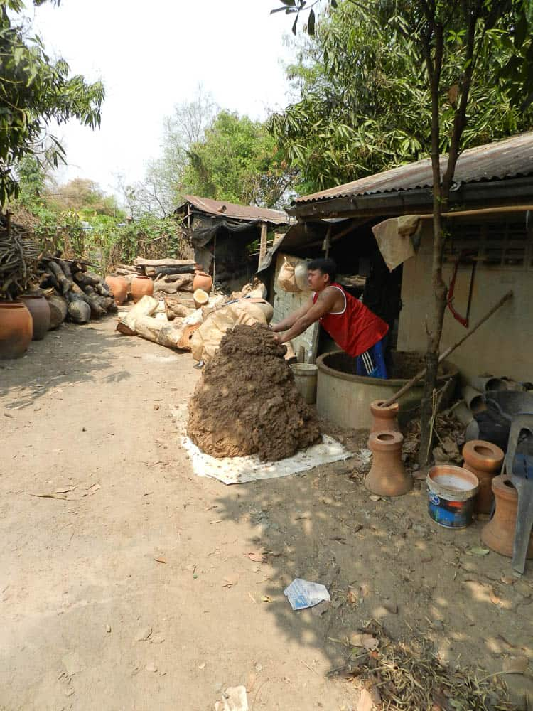Unloading soaked clay, background wood pile
