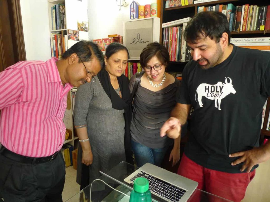 Pradyumna, Pushpa,	Minhazz and Ishan discuss an image.