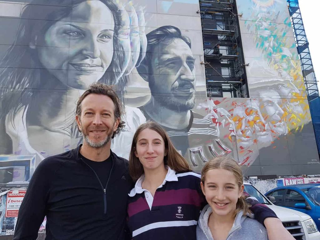Domenic Rodolfi with two of his daughters in front of Peter Seaton, Whispers of 10,000 Generations, 2017, Lygon Street, Brunswick, Melbourne, Australia