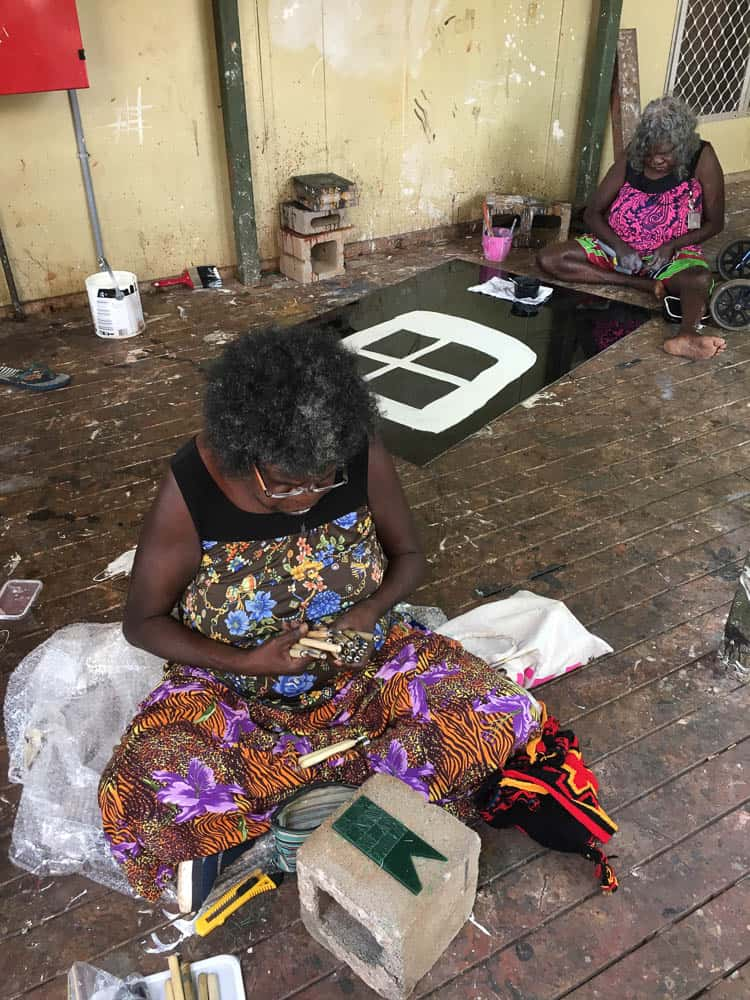 Marrnyula Mununggurr works on her series of pendants with her mother Nongirrnga Marawili painting behind her
