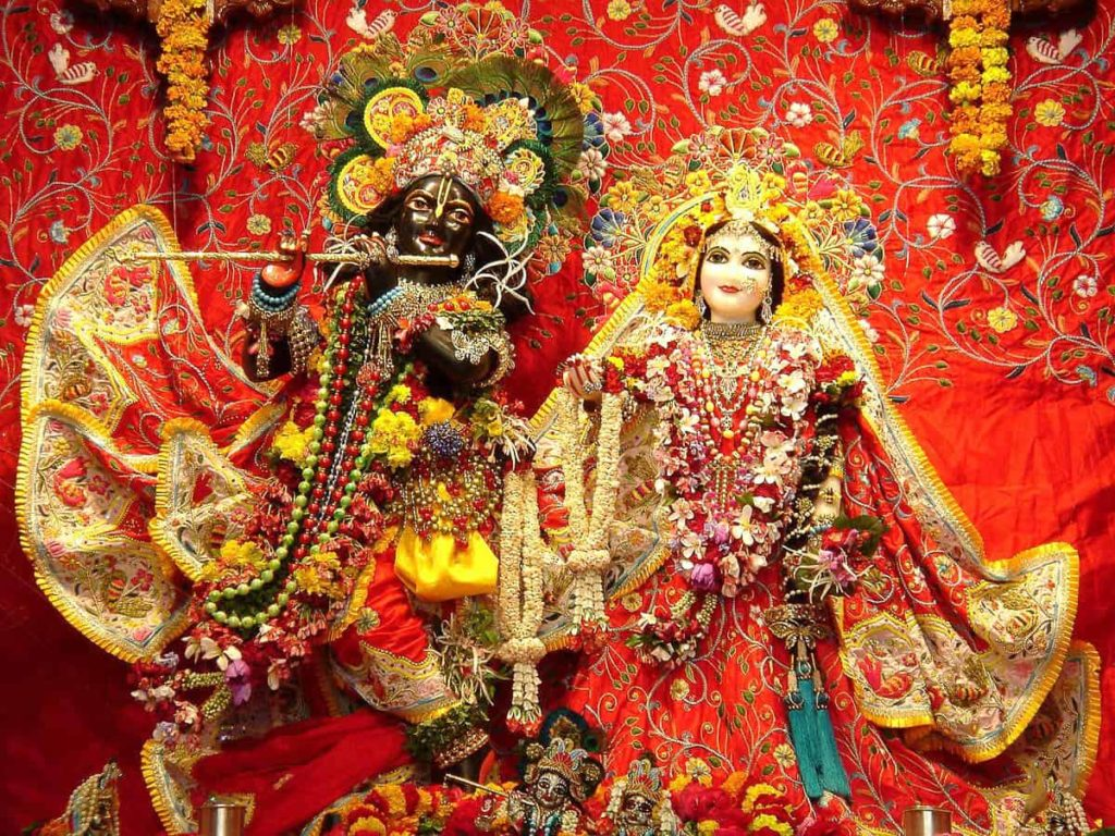 The idols of Krishna and Radharani, beautifully adorned in fine clothes and garlands at the Krishna Balarama temple.  Place: Vrindavan, India; Source: Sahadeva