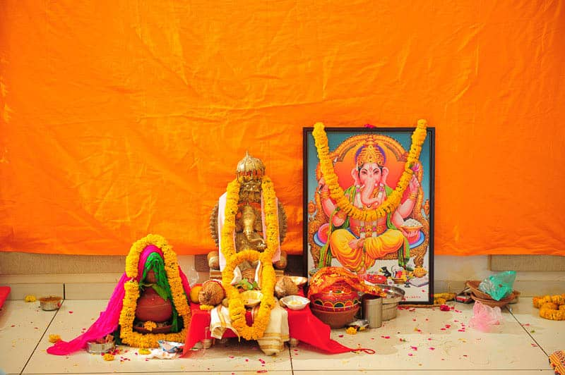 Different forms of gods and goddesses adorned with garlands of marigold during a puja. Place: Gujarat, India; Source: Author
