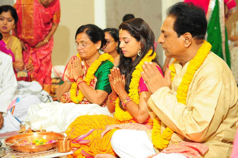 Members of a family taking part in puja also wearing garlands of marigold.  Place: Gujarat, India; Source: Author