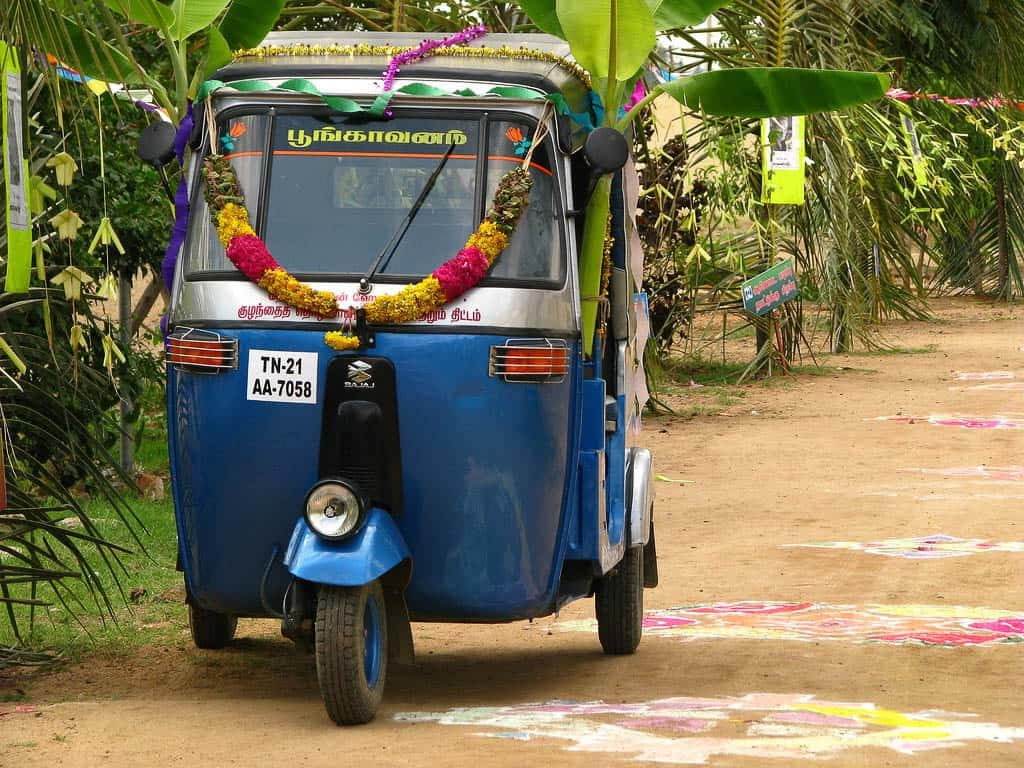 An auto-rikshaw adorned with a garland and banaba leaves during a festive occasion. Place: Tamil Nadu, India; Source: Flicker – McKay Savage