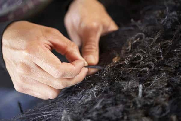 "Kohai's hands working on a ""black on black"" cloak. Muka (flax fibre), paru (mud dye) and rit (chemical dye), photo:Norm Heke"