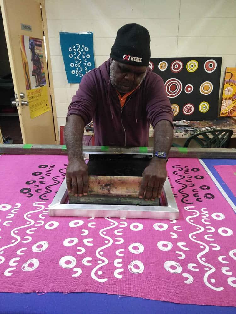 Albie Jack printing his design onto jute fabric – photo by Chrischona Schmidt/Ikuntji Artists