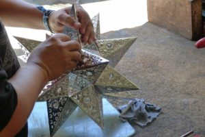 A relative of the Tinsmith at work soldering the points on a star 2013 photo Claire McArdle
