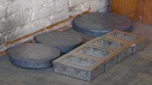 Circular lead blocks with a row of tin boxes in front 2013 photo Claire McArdle