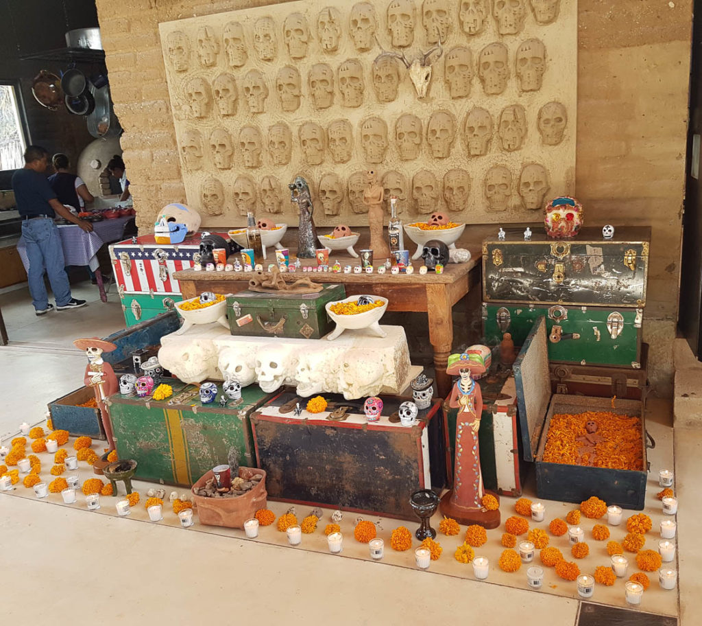 The ofrenda of Aden Paredes in memory of those who lost their lives in migration, featuring a clay skeleton in a suitcase filled with marigold.