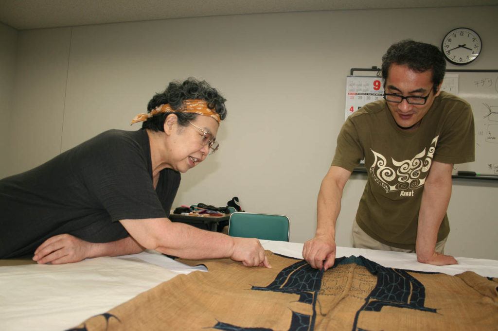 Tsuda and Nakatani Tetsuji, Tenri Sankokan Museum Curator,  focusing carefully on the robe; Tsuda pointing out the enlarged tsuno tokki and explaining her thesis about what these might mean – apotropaic qualities of the cloth itself…